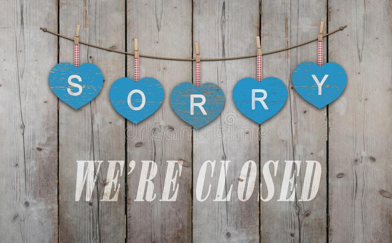 Blue wooden hearts with text sorry we are closed, on old scaffolding wooden backdrop. With copy space royalty free stock image