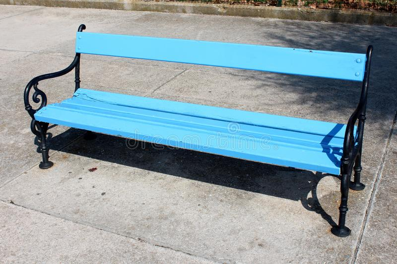 Blue wooden public bench with black wrought iron frame mounted on large concrete tiles sidewalk stock photography