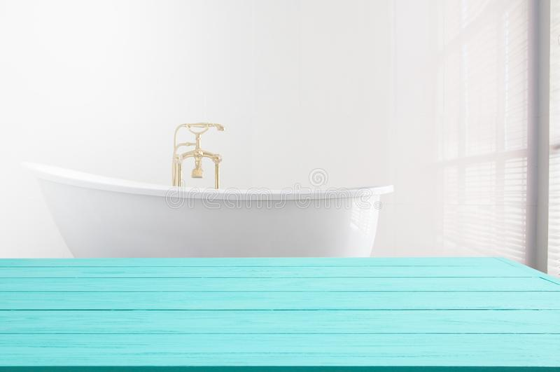 Blue wooden shelf on bathroom background. Wood desk table with top view and copy space near white bath at hotel. Room service. And shower spa concept. Selective royalty free stock photos