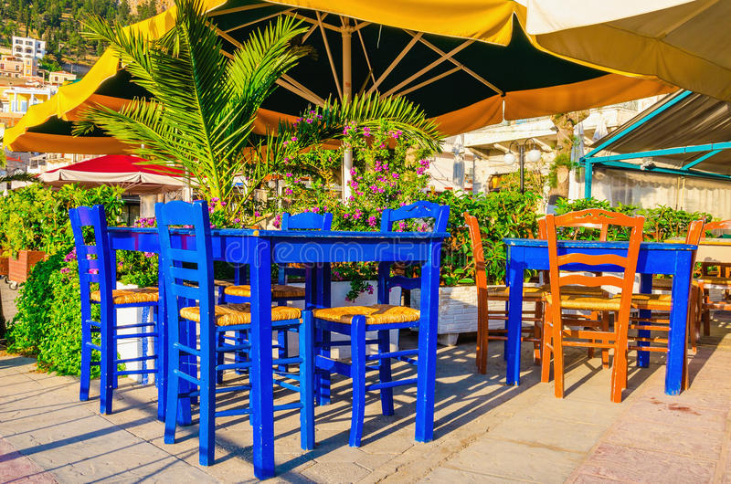 Blue wooden tables and chars in restaurant. Under umbrella royalty free stock photo