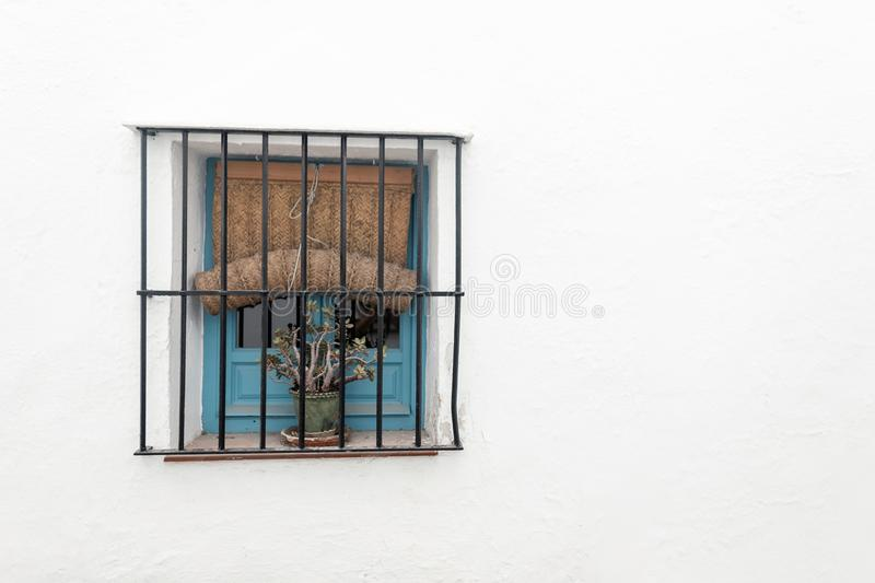 Blue wooden vintage window with iron bars and with a linen curtain on a white wall. White old house with one window stock image