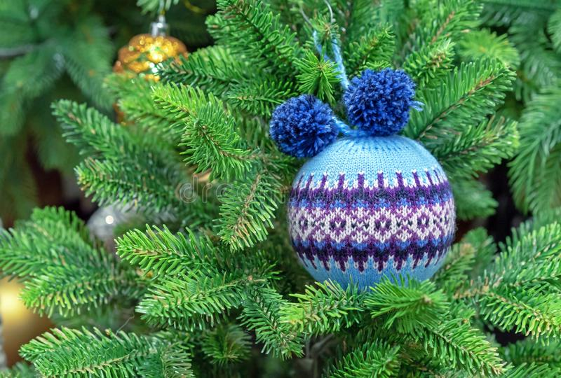 Blue woolen Christmas ball with a Scandinavian ornament on a green spruce stock photography