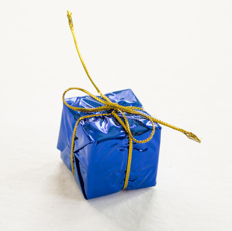 Blue wrapped gift on white background closeup. stock image