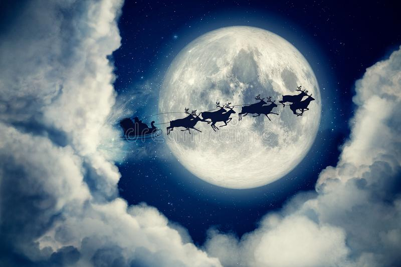 Blue xmas eve night with moon and clouds with Santa Claus sleight and reindeer silhouette flying to bring gifts and. Presents with text space to place logo or vector illustration