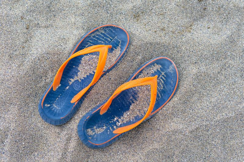 Blue-yellow beach slippers on the sea sand. Concept - rest, relaxation, travel, boat trip stock photography