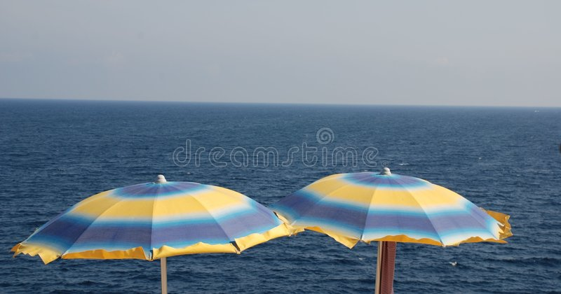 Blue and Yellow Beach Umbrellas. On a beach on a sunny summers day royalty free stock image