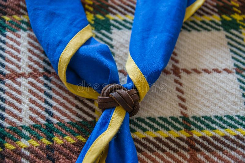 Blue ABS scout scarf with leather handmade scarf ring on woolen blanket. Blue with yellow border ABS scout scarf closed with scarf ring on brown woolen blanket stock photo