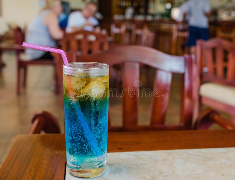 Blue and Yellow Cocktail in Cuba. Frosty yellow and blue alcoholic beverage, with condensation on the glass, served at a Cuban resort, background with people royalty free stock image
