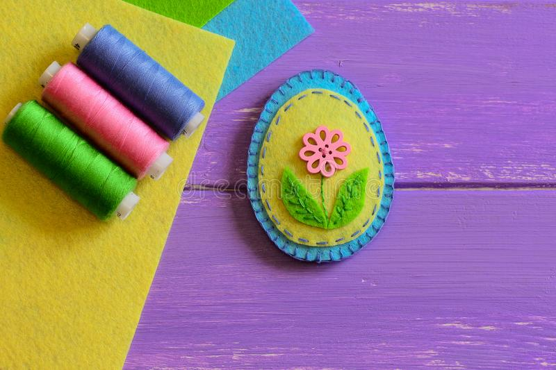 Blue and yellow felt Easter egg decor with pink flower. Adorable Easter crafts for kids. Small sewing projects. Easter crafts for kids. Fun DIY idea. DIY for kid royalty free stock photo