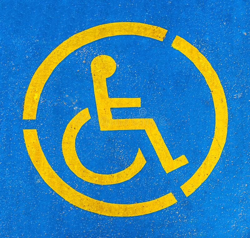 Blue And Yellow Handicap Parking Sign On Asphalt Persons With