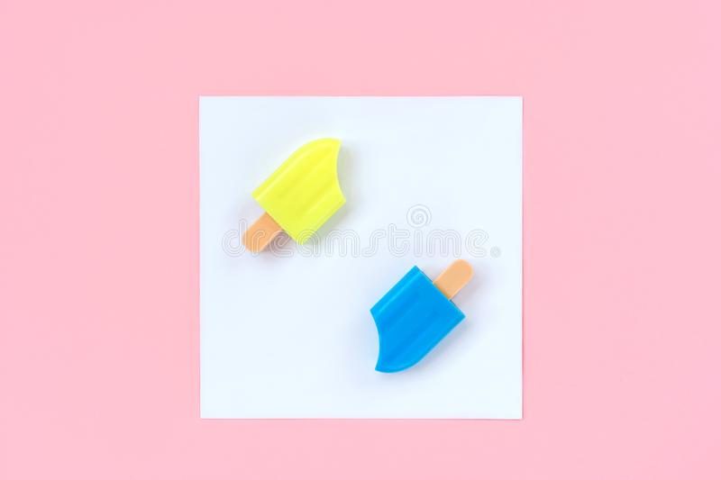 Blue and yellow ice cream in a white square on a pastel pink background royalty free stock photos