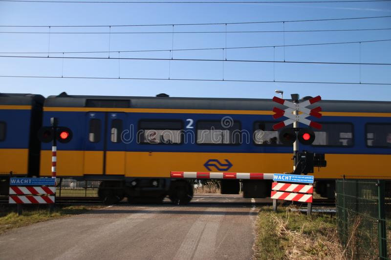 Blue yellow koploper intercity train at a railroad crossing in Moordrecht the Netherlands. stock photo