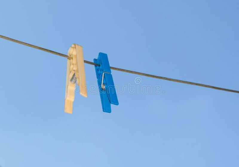 blue-and-yellow-pegs-on-clothes-line stock photo