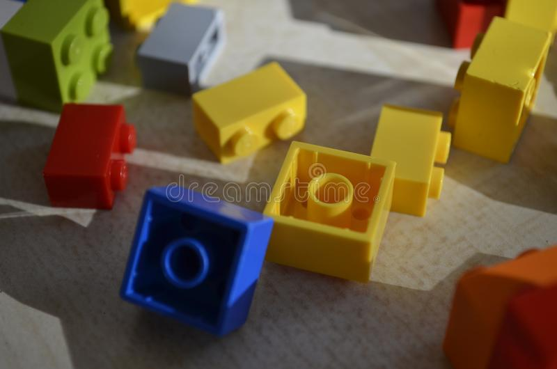 Coloured lego blocks on table. Blue, yellow, red, green, grey, orange double and single lego blocks on cream backing with shadow stock photography