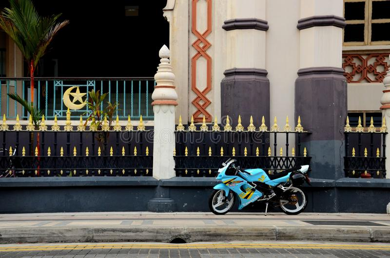 Blue yellow sporty motorcycle parked on pavement stock photography