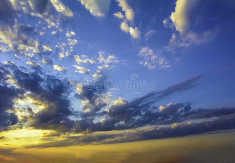 Blue yellow sunny sky and clouds background of dramatic cloudscape and skyscape with clouds in sunset stock photo