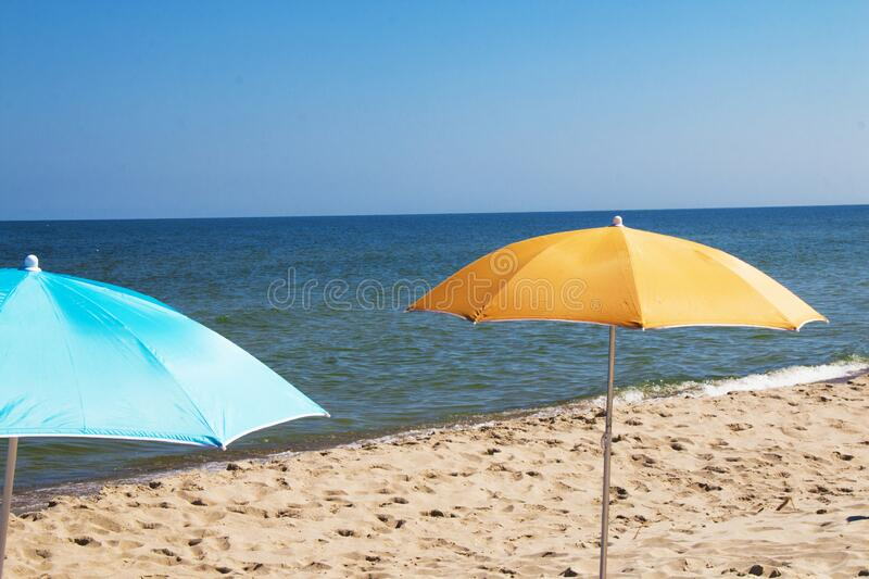 Blue and yellow umbrellas on hot sandy beach with blue sea and sky in the background stock photography