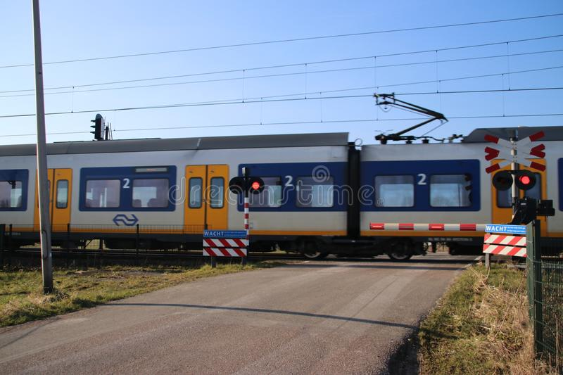 Blue yellow white sprinter train at a railroad crossing in Moordrecht stock photos