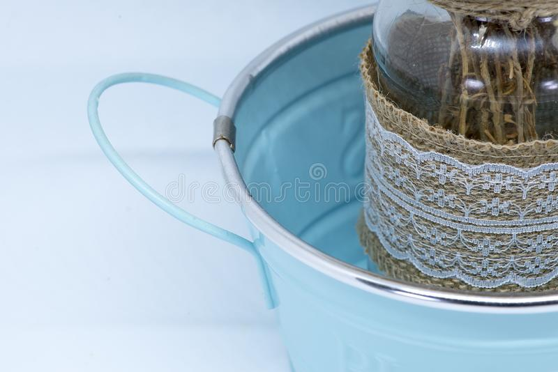 Blue zinc bucket with glass jar and dried flowers.  stock images