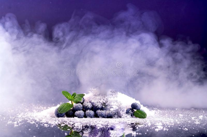 Blueberries on background of snow and smoke. Purple fashionable color.Holiday and celebration concept. Close up royalty free stock photos