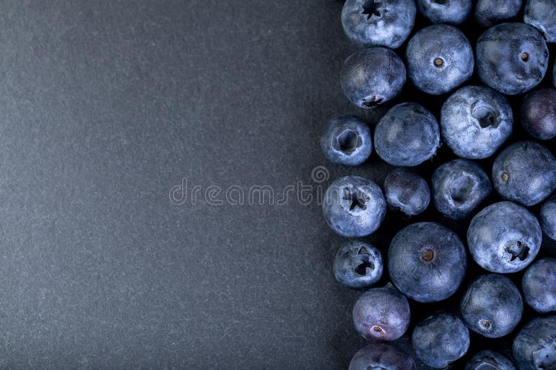 Blueberries on black stone board. Fresh and ripe blueberries on dark stone plate stock photos