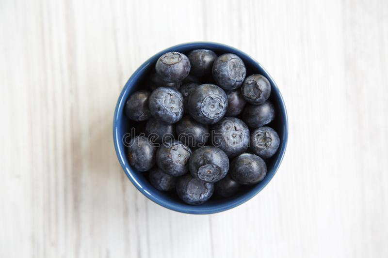 Blueberries in a blue bowl, top view. Fresh bilberry on white wooden table. stock image