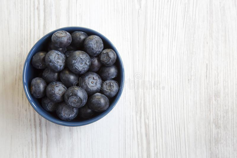 Blueberries in a blue bowl, top view. Organic superfood. Copy space royalty free stock photos