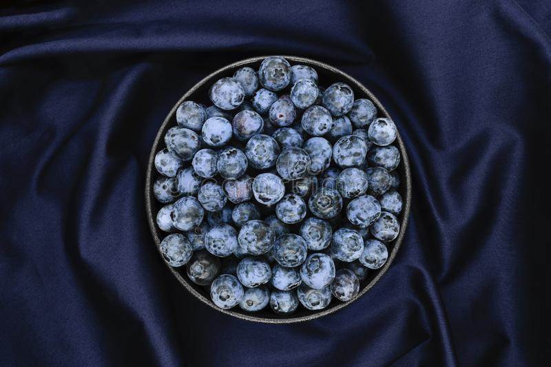 Blueberries on blue fabric background stock photography