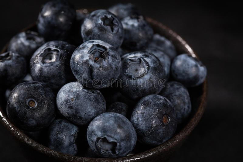 Blueberries in a brown ceramic bowl placed on a black. Tablecloth royalty free stock photos