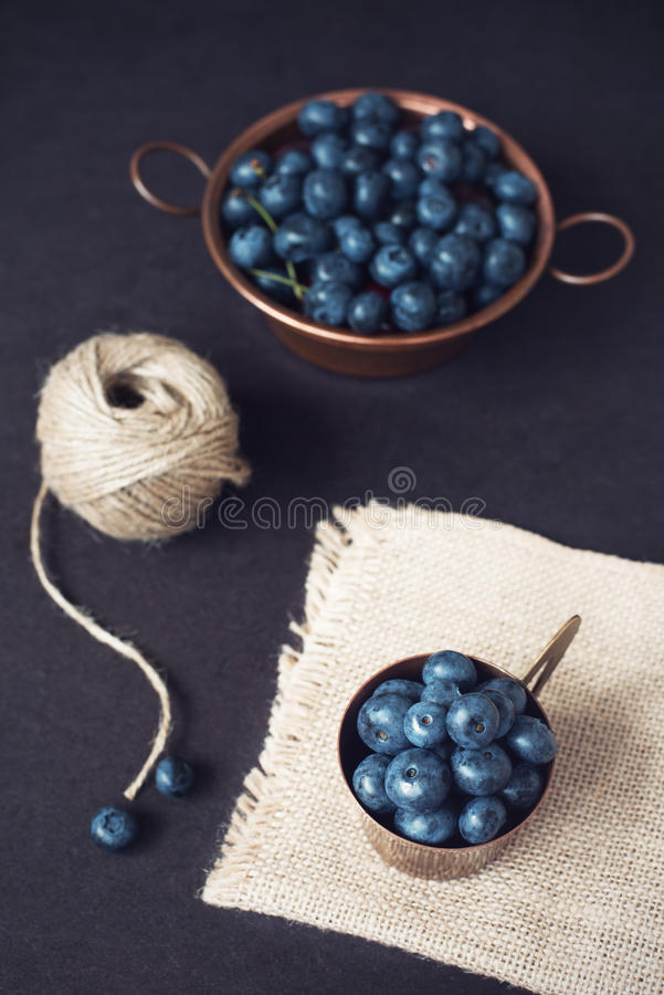 Blueberries dark picture. Fresh fruits, berries in an old copper cup. Dark Styled Stock Photo, Black Background royalty free stock images