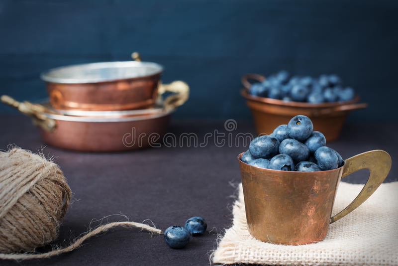 Blueberries dark picture. Fresh fruits, berries in an old copper cup. Dark Styled Stock Photo, Black Background stock photography