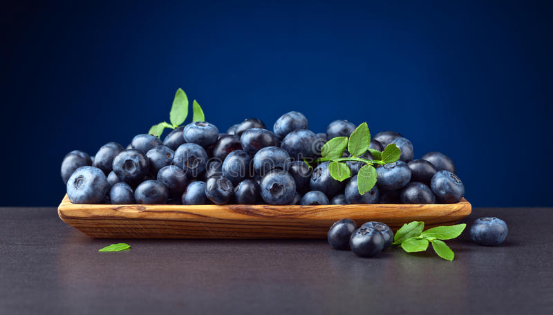 Blueberries with green leaves in wooden dish stock photo