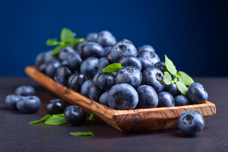 Blueberries with green leaves in wooden dish royalty free stock images