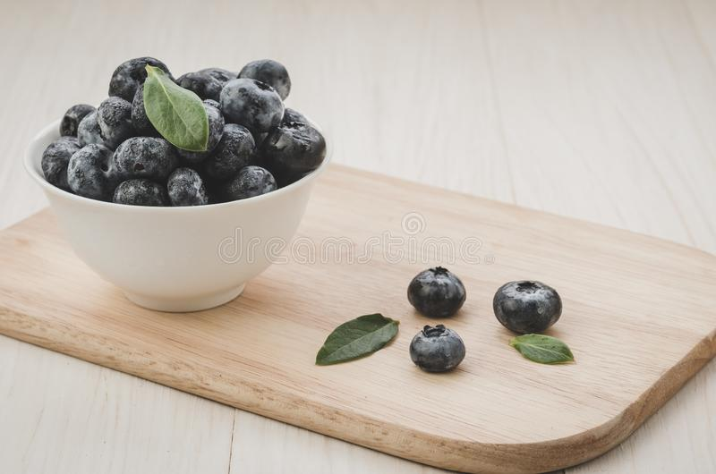 Blueberries with leaves in bowl on a wooden tray/Blueberries with leaves in bowl on a wooden tray. Copy space. Toned stock image
