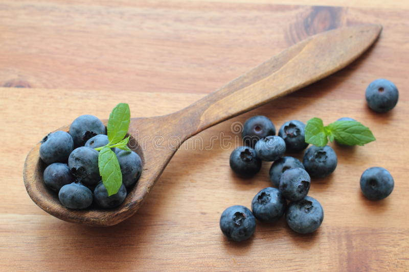 Blueberries with mint leafs. Healthy blueberries fruits on a wooden spoon royalty free stock photos