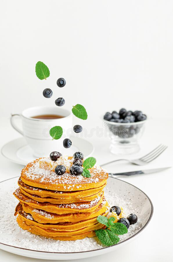 Blueberries and mint leaves falling on a stack of pancakes. American dessert. For breakfast stock images