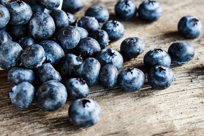 Blueberries on old wooden table. Close up of blueberries on old wooden table, Organic fruits stock photography