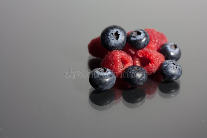 Blueberries and raspberries on black background royalty free stock photo