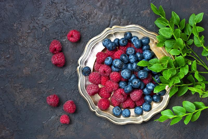 Blueberries and raspberries. Food background. Ripe and juicy fresh picked berries closeup. Blueberry and raspberry on dark  background. Top view  with copy space stock photos