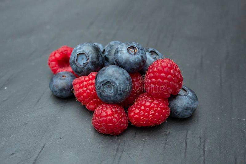Blueberries and Raspberries on a Grey Slate stock photos