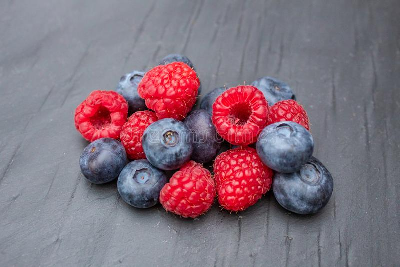 Blueberries and Raspberries on Grey Slate in the Kitchen royalty free stock photos