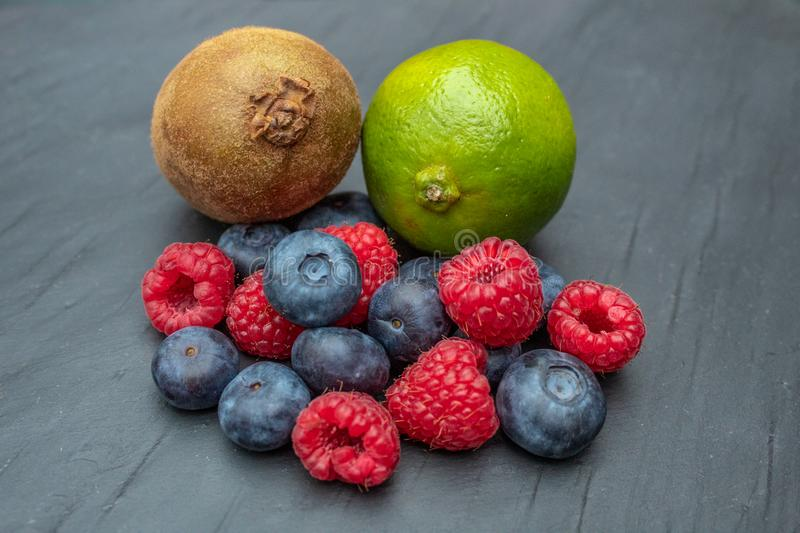 Blueberries, Raspberries, Lime and Kiwi Fruit on a Slate stock photography