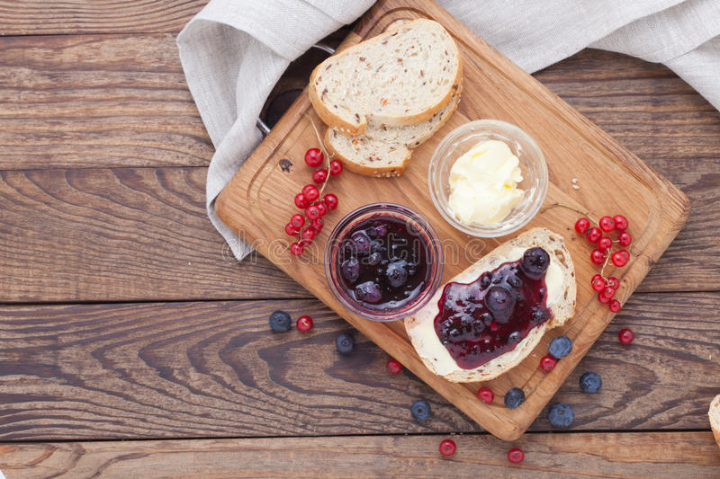 Blueberries and red currants jam, butter and bread on wooden table. stock photo