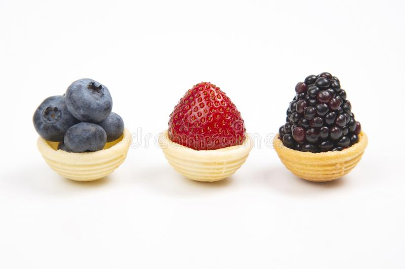 Blueberries, strawberries and blackberries in waffle baskets on a white background royalty free stock photos