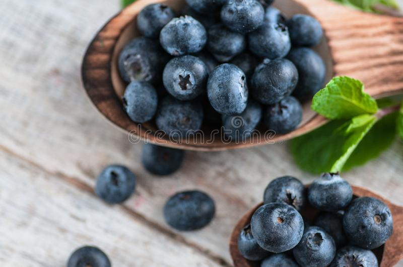 Blueberries and various forest fruits, raspberries, strawberries. There are different types of wood on the table. royalty free stock image