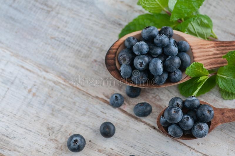 Blueberries and various forest fruits, raspberries, strawberries. There are different types of wood on the table. stock image