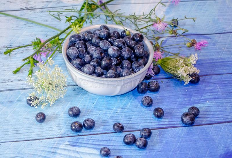 Blueberries and wild flowers on blue planks stock photography