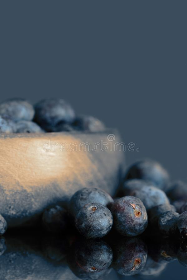 Blueberries in a wooden bowl and on glass background. With toning royalty free stock photos