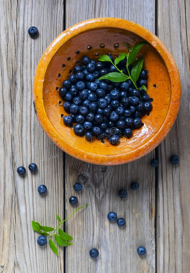 Blueberries  in a yellow bowl. On the wooden table royalty free stock photos