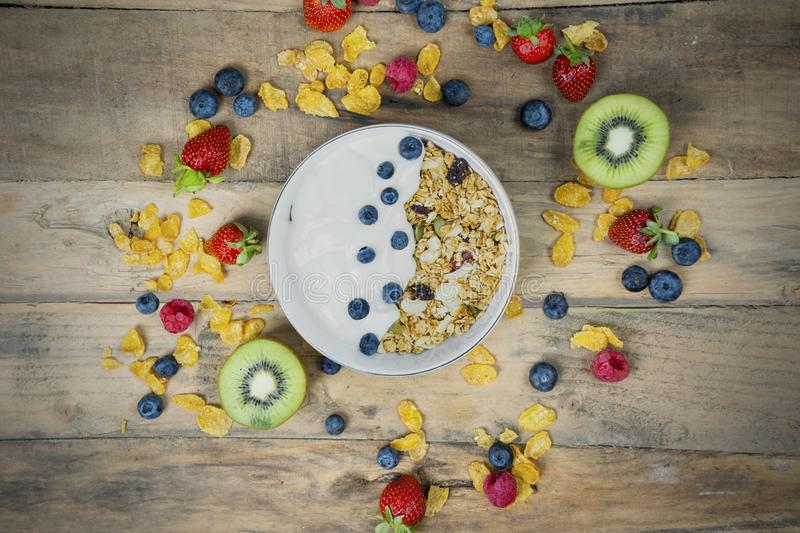 Blueberries with yogurt and cornflakes in a bowl. High angle view of blueberries with yogurt and cornflakes in a bowl. Shot on a wooden table royalty free stock photography